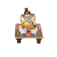 Ganesh statue sitting on chowki